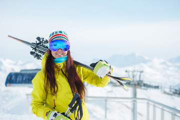 Sports woman in mask with skis on her shoulder on background of snowy hill, blue sky in winter