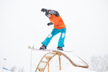 Image of young sportive man skiing on snowboard with springboard