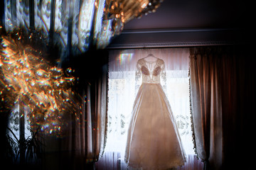 Look from behind the lamp at rich wedding dress hanging on the mirror