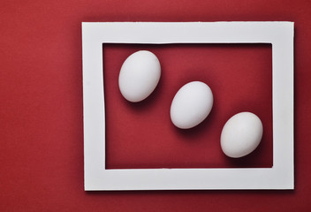 Three white chicken eggs in a white frame on a red background. Minimalist trend.