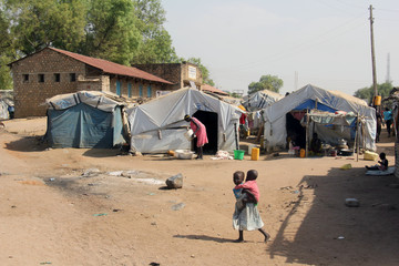 A child carries her sibling as they walk within the makeshift shelter in Konyokonyo camp for the internally displaced people in Juba