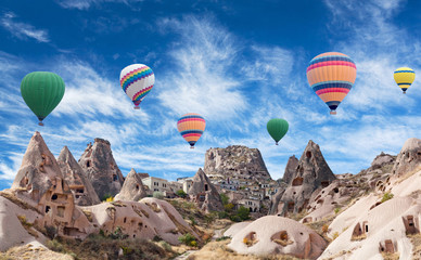 Uchhisar fortress and colorful hot air balloons flying over valley in Cappadocia, Anatolia, Turkey