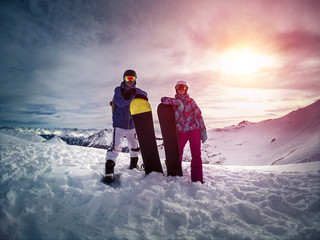 Couple smiling with snowboarding outside in the mountains at sunset. Mountains in the Alps - Ischgl town in Austria.
