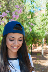 young and brunette girl with long hair with a blue cap in the park