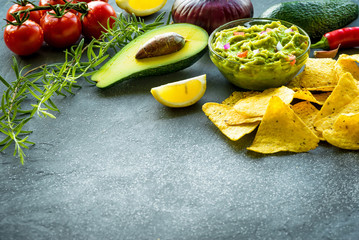 Guacamole bowl with ingredients and tortilla chips on a stone table. Selective focus. Copyspace for your text.