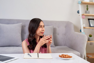 Young asian woman enjoying a tea break and snack while working at home.