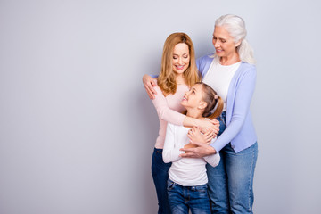 Family concept. Portrait of adorable lovely cute family generation standing hugging together wearing casual clothed isolated on gray background copyspace