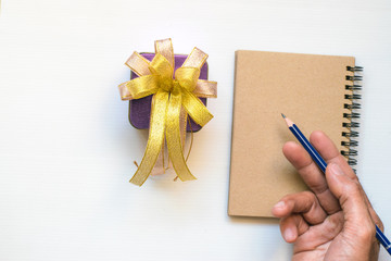 Notepad with pencil gift ribbon on wood board background.using wallpaper for education, business photo.Take note of the product for book with paper and concept, object or copy space.