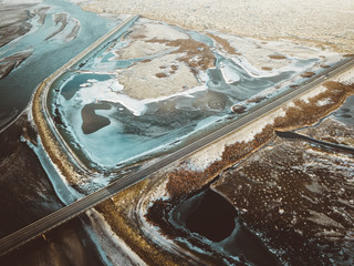 Aerial view of Iceland winter texture, frozen glacier river, bridge, road, delta of river, volcano, black sand, mountains, abstract landscape