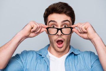 Close up portrait of astonished, shocked, attractive guy holding eyelets of glasses on his face with fingers, having wide open mouth, looking out spectacles, isolated on grey background