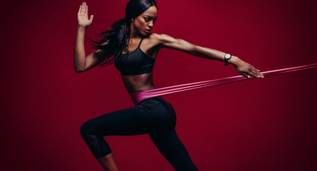 Strong woman using a resistance band in her exercise routine Wall mural