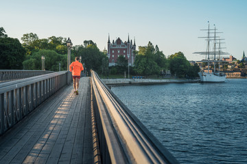 Young man runs on the bridge to the Skeppsholmen island in Stockholm at sunrise.
