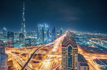 Scenic nighttime skyline of a big modern city. Dubai, UAE. Aerial view on famous highway interchange and skyscrapers.