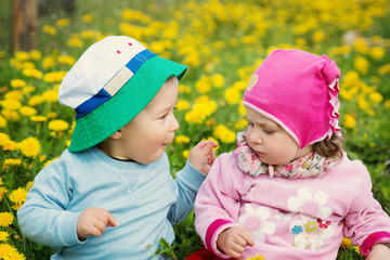 Little boy and girl in hats sitting on the field with soft toys in summer