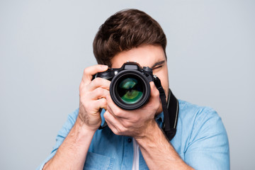 Portrait of guy in jeans shirt looking at photo camera, shooting photographs during excursion, making photosession over gray background