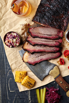 Fresh Brisket BBQ beef sliced for serving against a kraft paper background with sauce, hot peppers and corn.