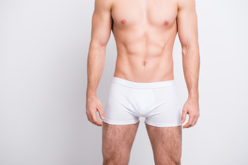 Men's health concept. Cropped close up photo of man's intimate zone, he is wearing white underlinen boxer-shorts isolated on gray background copy-space