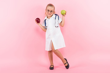 Little girl in doctor costume with apples