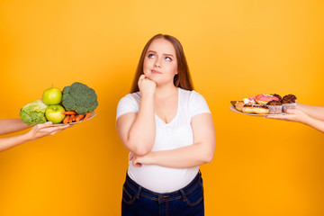 Young woman making choice between healthy and unhealthy food