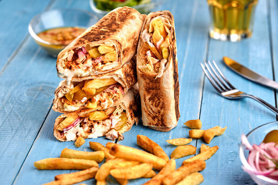 Shawarma chicken roll in a pita with fresh vegetables, cream sauce and french fries on wooden background. Selective focus