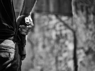 black and white image of male holding handgun in holster ready to shoot in shooting competion