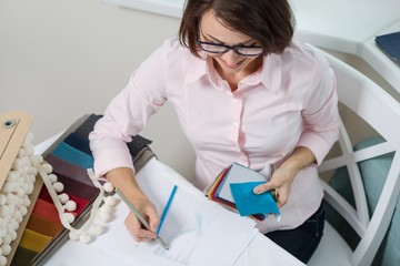 Woman interior designer, works with samples of fabrics for curtains and blinds.