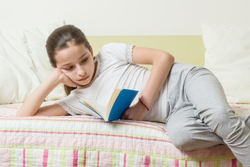 Teenage girl 10 years old in home clothes reads a book on the bed in her room