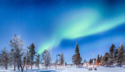 Aurora Borealis over winter wonderland scenery in Scandinavia