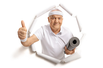 Elderly sportsman breaking through paper and making a thumb up sign