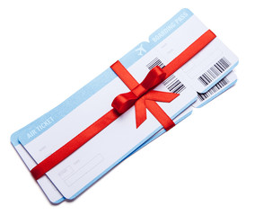 Air tickets as a gift with a red ribbon and bow. Isolated on white background