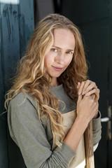 Portrait of confident blond woman wearing apron