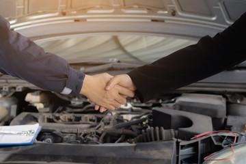 Repair man and woman handshake front of car.