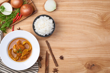 spicy chicken and rice on wooden background