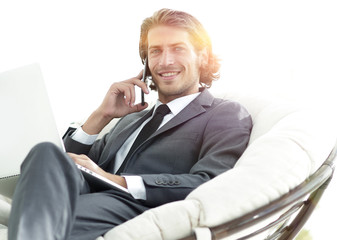 businessman talking on smartphone sitting in chair in his house