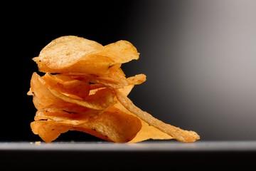 Kartoffel Chips gestapelt im Spotlight - vor schwarzem Hintergrund