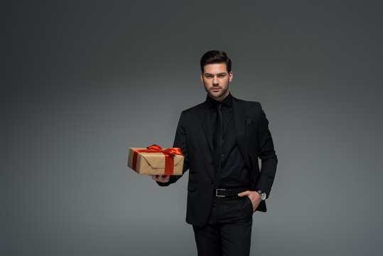 Stylish man in black suit holding gift box isolated on grey, international womens day concept