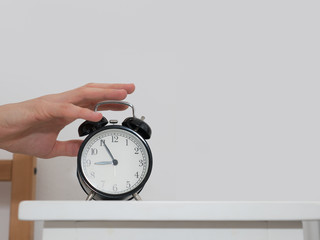hand try to stop alarm clock beside bed