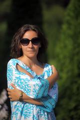 beautiful brunette in summer in blue dress and sunglasses