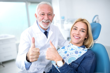 Smiling and satisfied experienced dentist and young patient after successful treatment