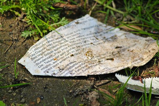 Verwitterter alter Zettel mit Typografie Schrift auf Boden im Gras