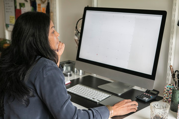 Side view of businesswoman using computer while sitting at home office