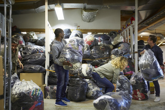 Colleagues stacking plastic sacks in warehouse