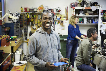 Portrait of smiling mid adult volunteer holding digital tablet with colleagues working in background at workshop
