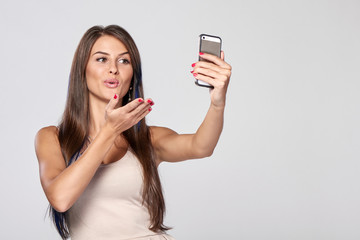 Closeup of beautiful smiling brunette woman taking self portrait on smart phone sending a kiss, over grey background