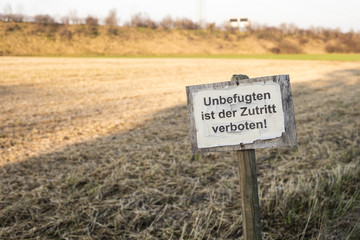 """Grunge and old signboard in countryside's crop field with text in german meaning: """"Access to people without permission is prohibited"""""""