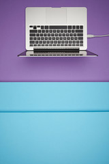 top view of laptop on purple and blue paper background