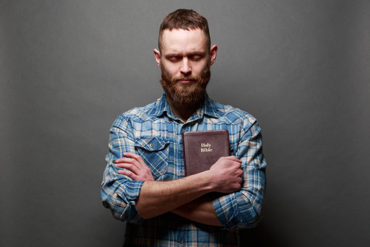 Handsone man reading and praying over Bible in a dark room over gray texture