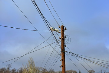 Wooden electric pole with wires on the street in the city against a blue sky.