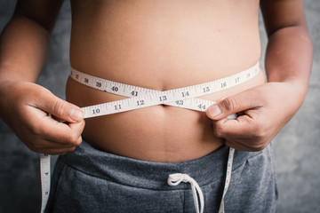 Portrait fat boy measuring tape of stomach,healthy and lose weight concept ,selective and soft focus