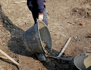 Man at work with shovel, pick and bucket on a rough ground to cultivate.